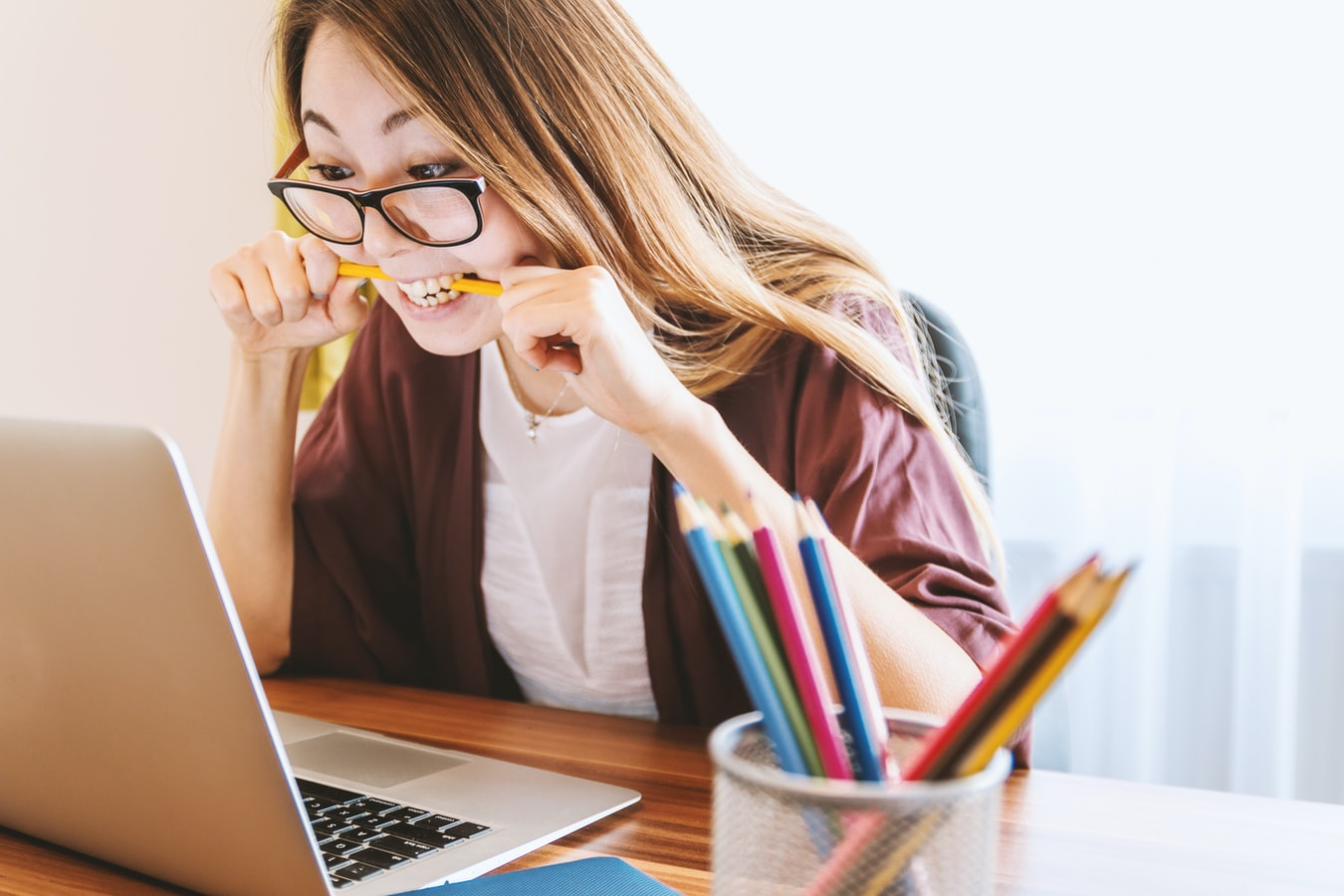 Woman biting on yellow pencil looking at laptop