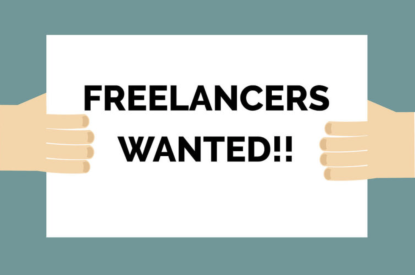 """Two hands holding up a sign saying """"freelancers wanted."""""""