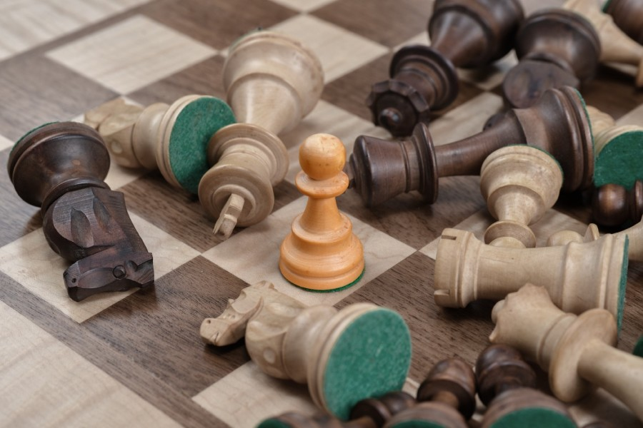 Wooden chess pieces spread on chess board