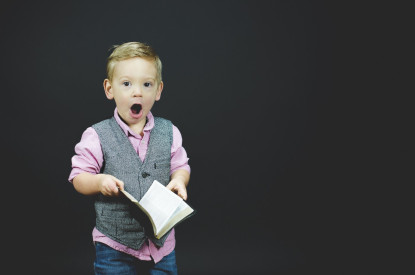 Young boy holding book, with surprised look on his face