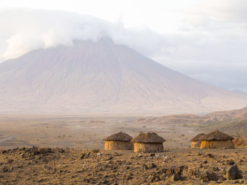 Mt Ol Doinyo Lengai with Maasai huts in the foreground