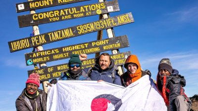 Group photo of trekkers sitting in front of Uhuru Peak sign and holding Follow Alice flag