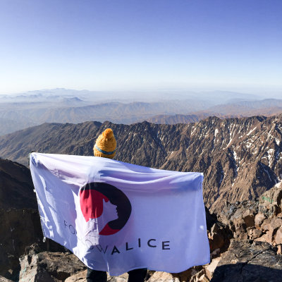 Client stands with Follow Alice flag on mountain