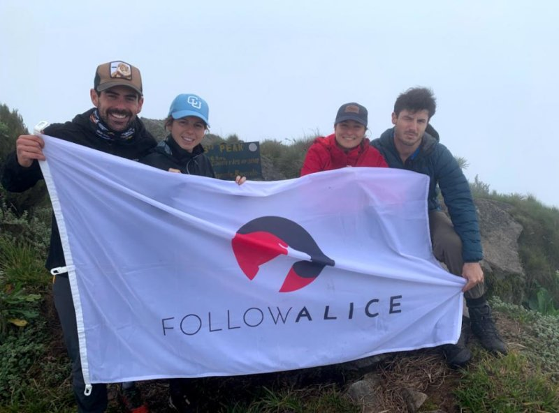 Follow Alice flag held by hikers crouching down, best time to visit Uganda