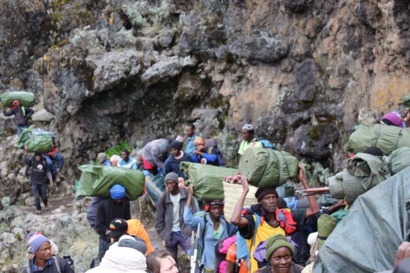 Guides and porters working hard on incline on Kilimanjaro