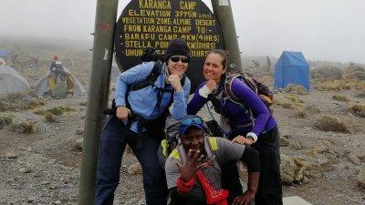 Smiling trio at camp sign on Kili