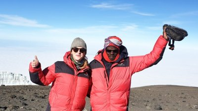 Tash and Chris at summit of Kilimanjaro on a clear, sunny day and waving at the camera with the glacier behind them