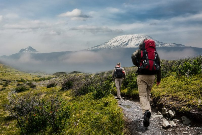 Kilimanjaro in distance with trekkers in foreground, Best time to visit Tanzania