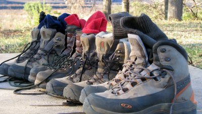Four pairs of hiking boots and socks lined up alongside each other