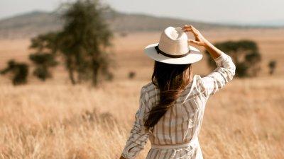 Woman in safari hat in field of grass