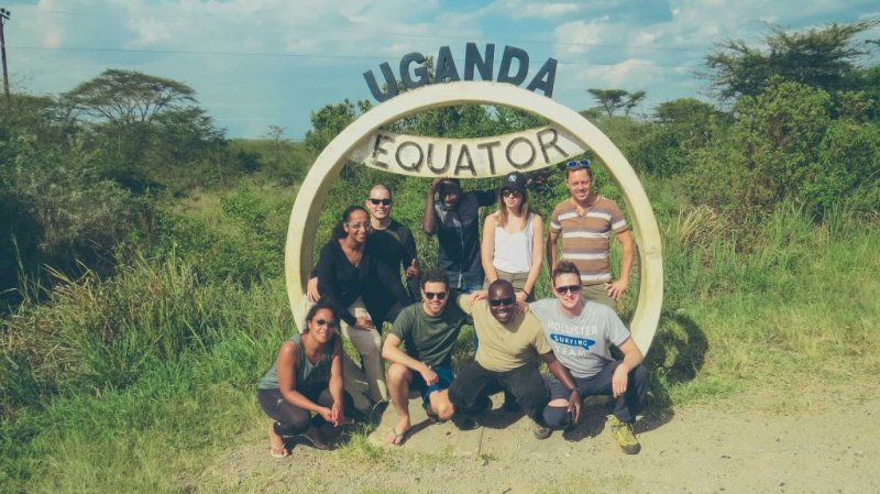 Group of travellers standing by the Uganda Equator sign
