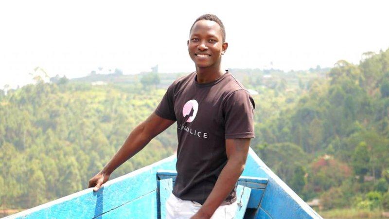 Smiling man with green Ugandan landscape in background