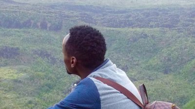 Young African man in yellow boots and wearing a checked backpack sitting on rock high above green landscape