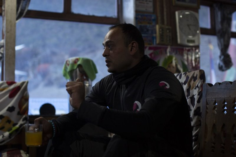 Man in Follow Alice top in teahouse in Annapurna