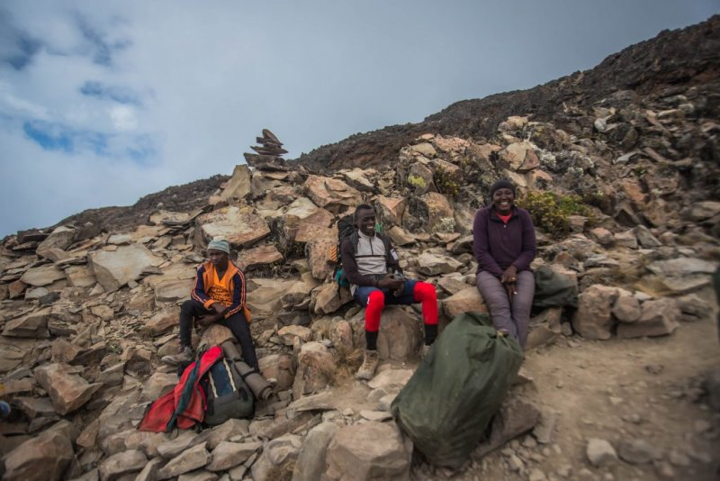 Follow Alice porters resting on the mountainside o fKilimanjaro
