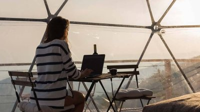 Woman sitting at desk in hotel room with views of hills