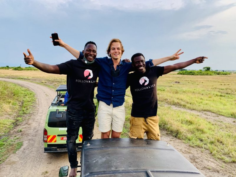 Men smiling while standing on a safari vehicle in a Uganda game park
