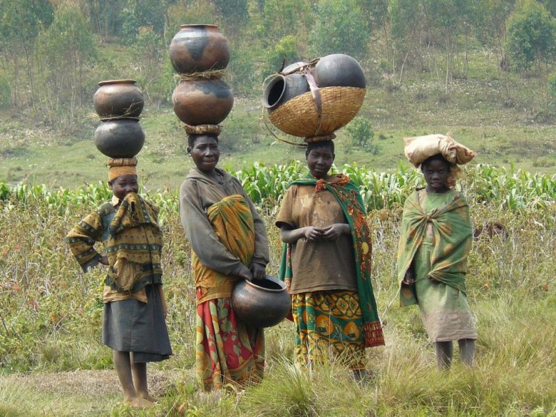 Batwa women and girls standing in a field and balancing pots on their heads
