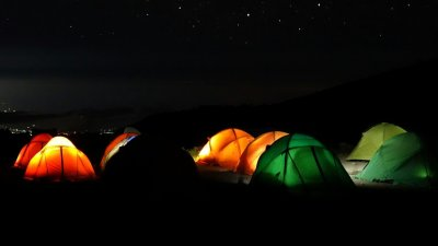 Starry sky over Kilimanjaro campsite with orange and green dome tents lit up from within