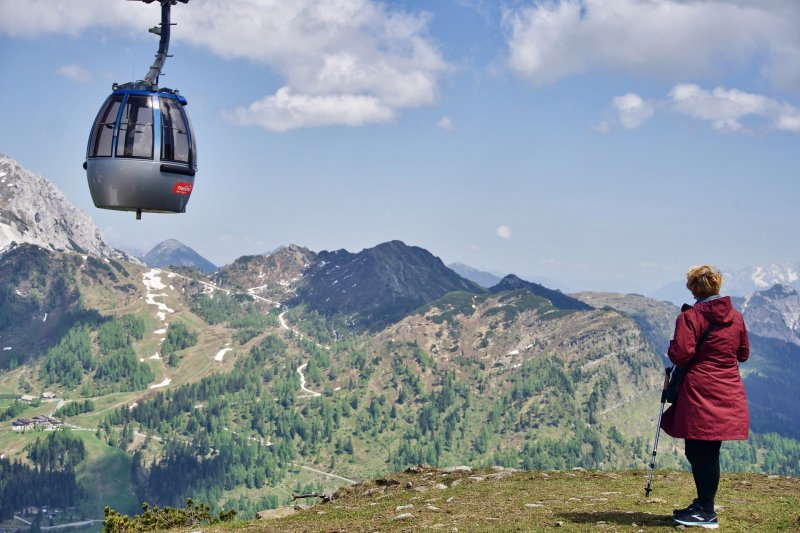 Woman hiker in Alps with cable car overhead