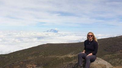 Tash sitting on a rock on Kilimanjaro with cloud bank below