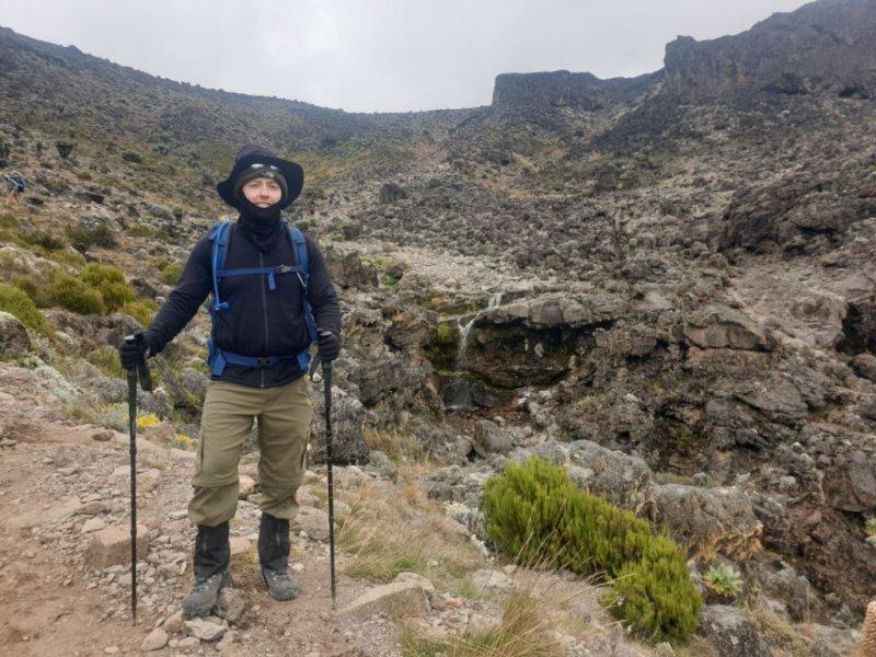 Trekker in warm gear standing by waterfall near Barranco Camp on Kilimanjaro