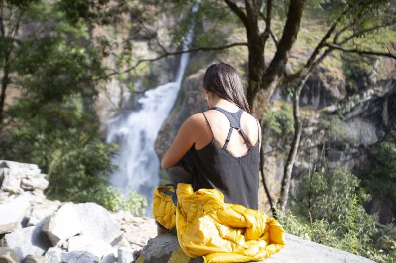Woman and waterfall along the Annapurna Circuit route in Nepal