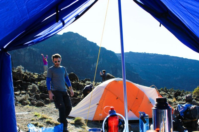 Man outside tent on Kilimanjaro