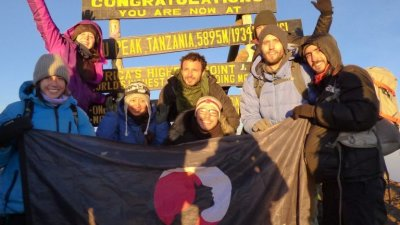 Group photo at Uhuru Peak on a sunny day with the Follow Alice flag