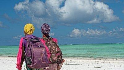 Women wearing backpacks walking along the beach in Zanzibar