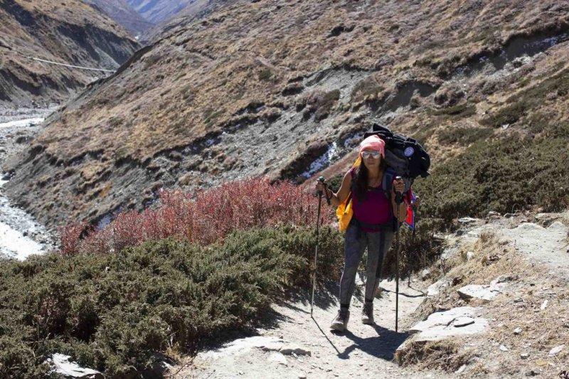Girl trekking along path of Annapurna Circuit route in Nepal