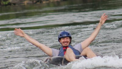 Man in hard hat with arms raised as he moves down river on the Nile while sitting in an inflated tube