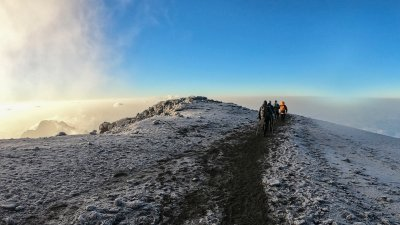 Trekkers walk a trail through snow-encrusted scree at the summit of Mount Kilimanjaro with a blue morning sky overhead
