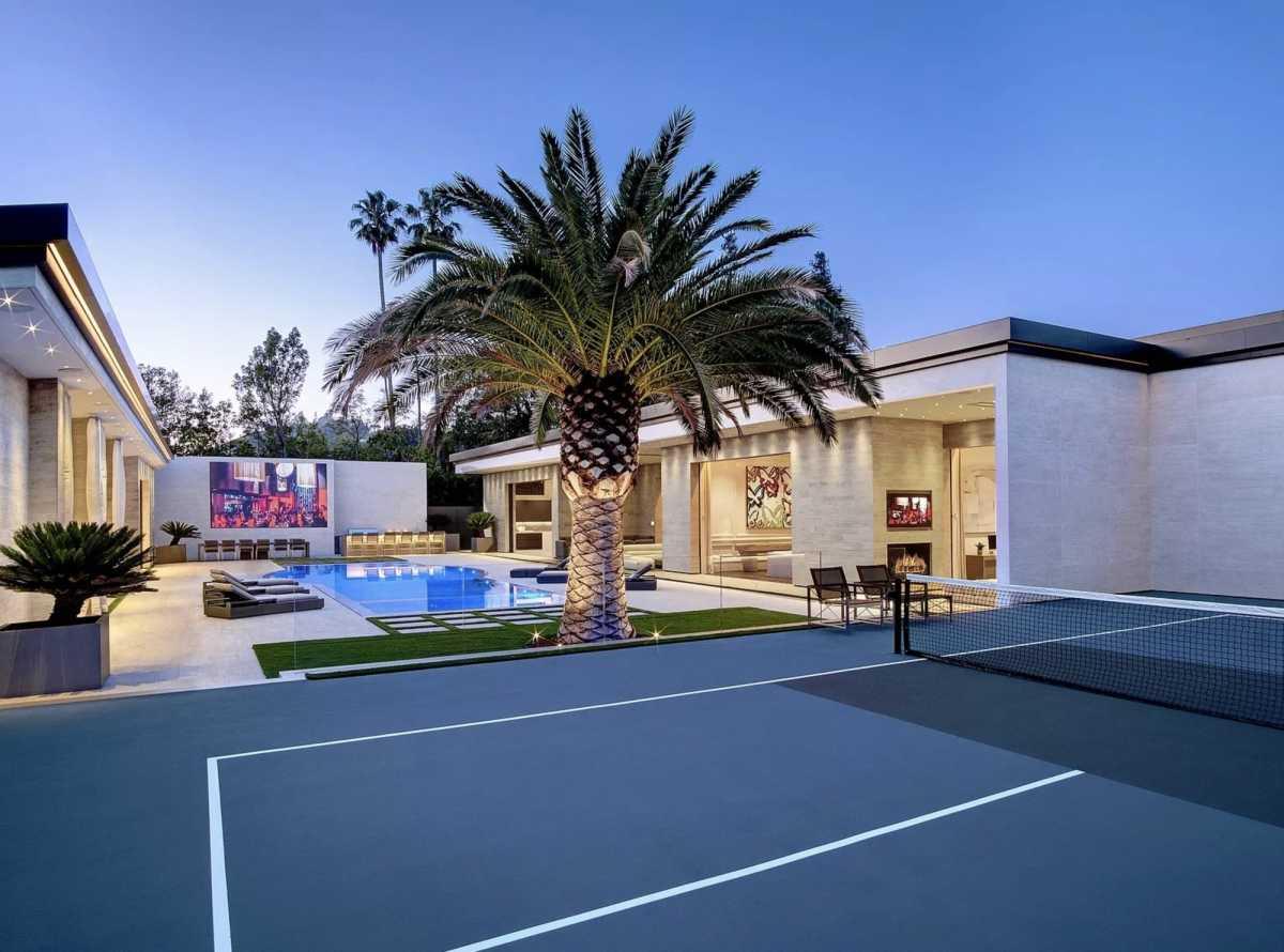 La cancha de tenis está al lado de la piscina.
