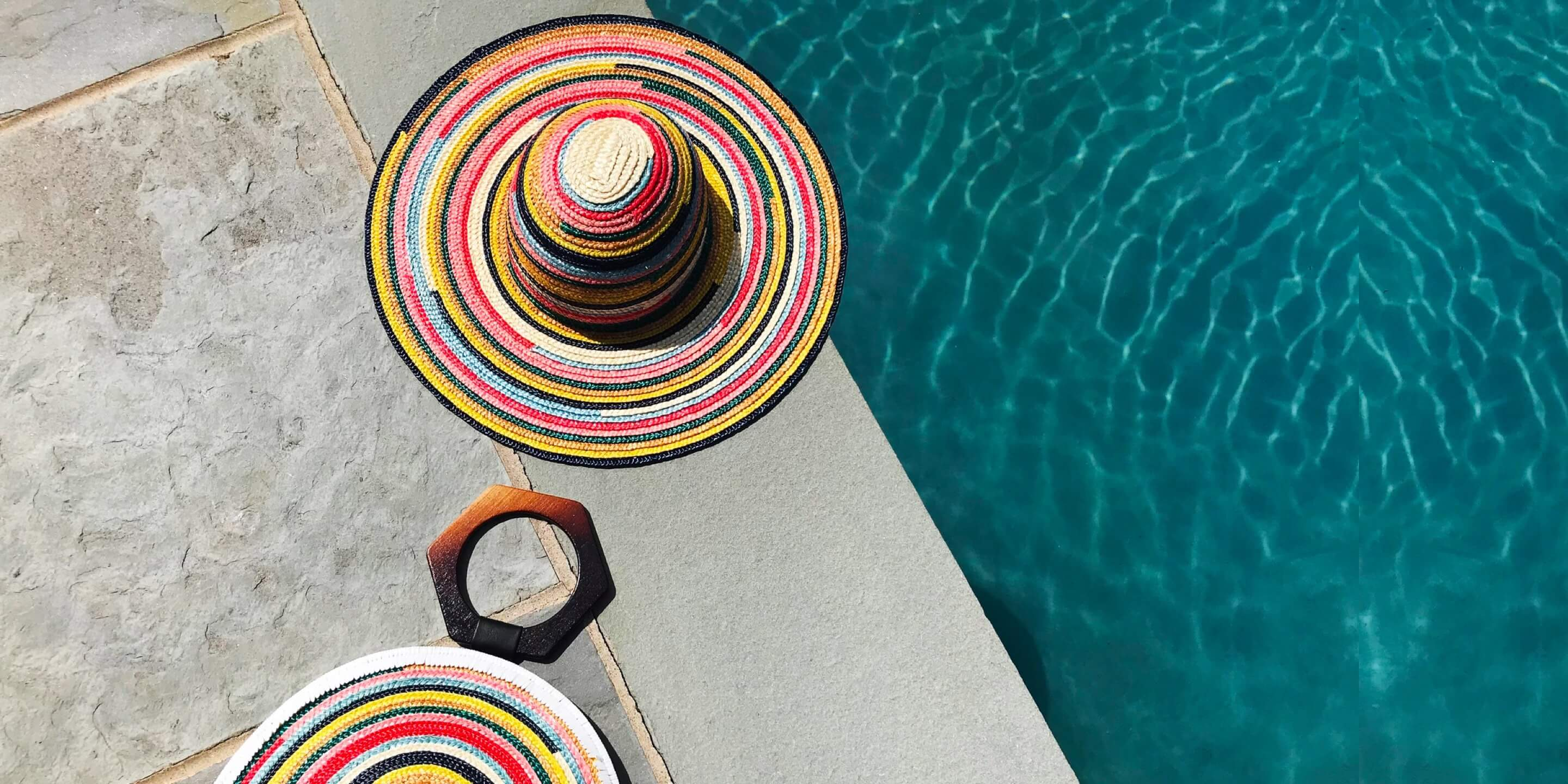 eugenia kim hats next to swimming pool