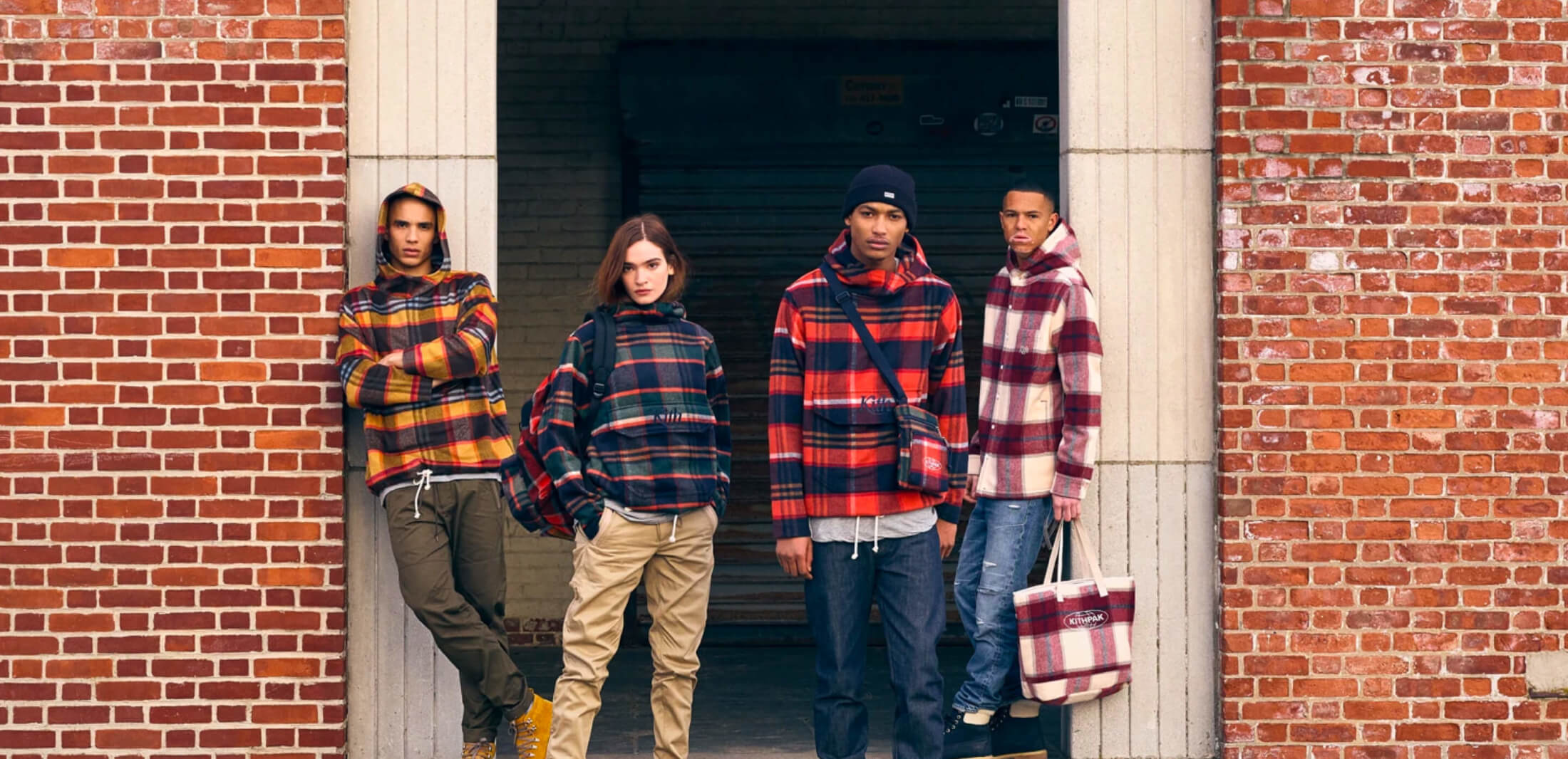 group of young people outside building wearing kith clothes