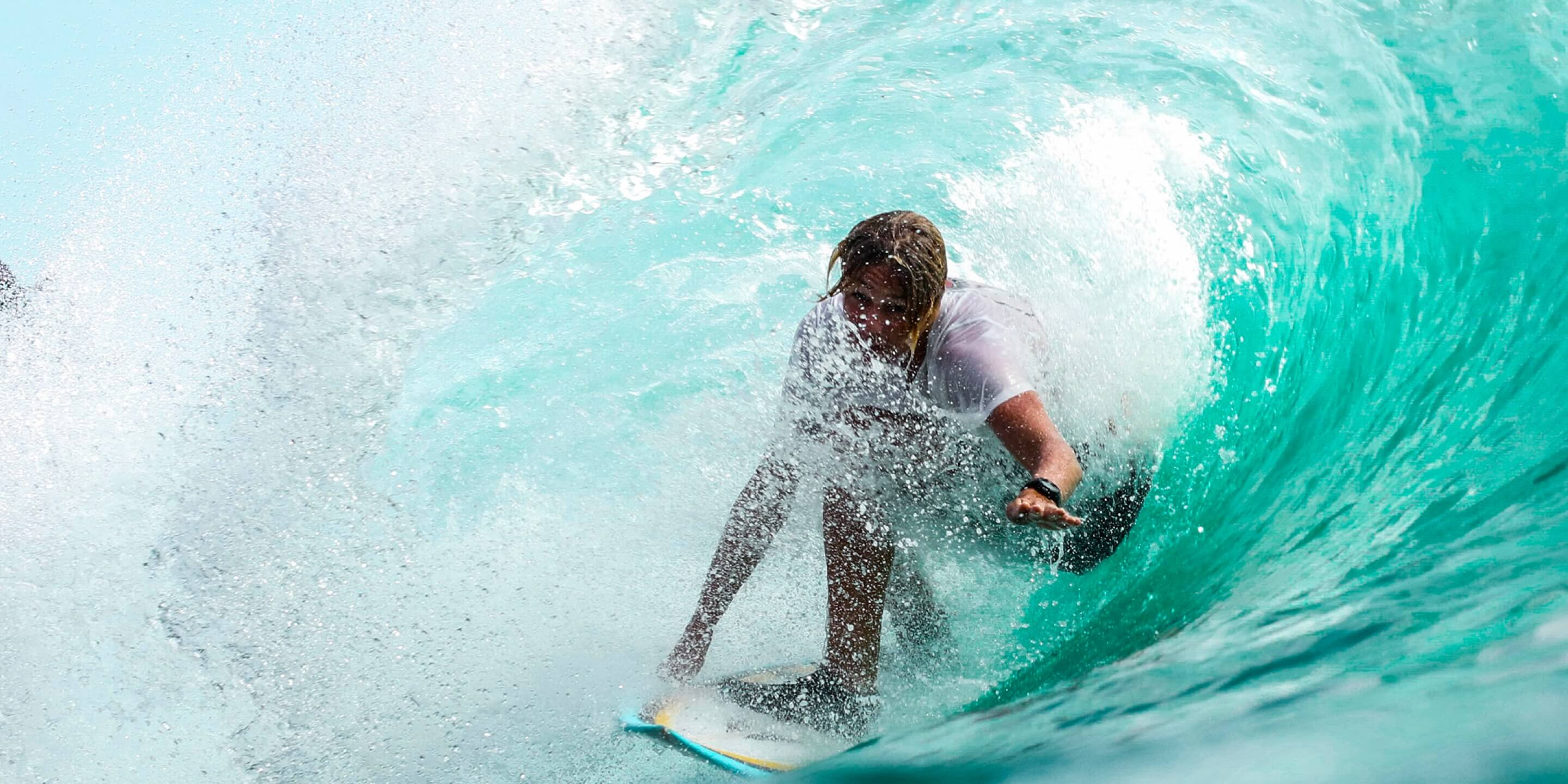 man shreds wave on surfboard