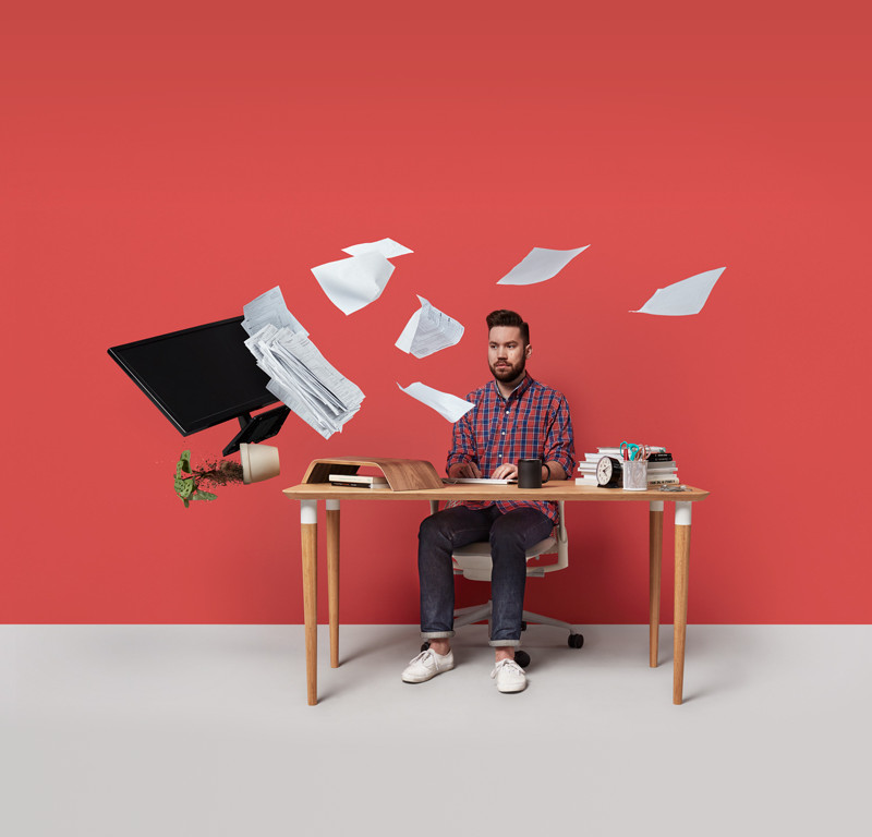 A man sits at his desk while his files fly about as though possessed.