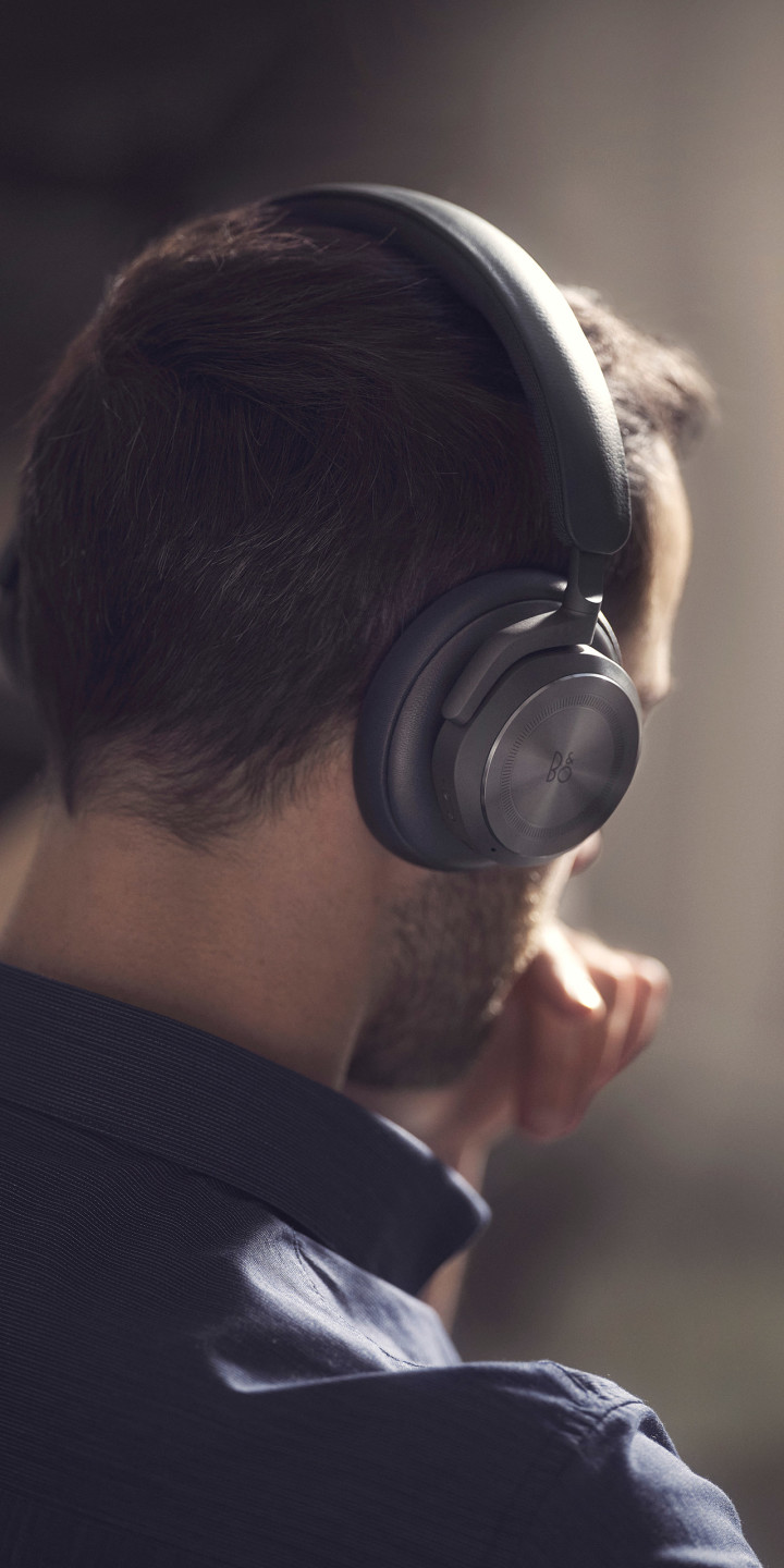 A man wearing Beoplay HX Black while working