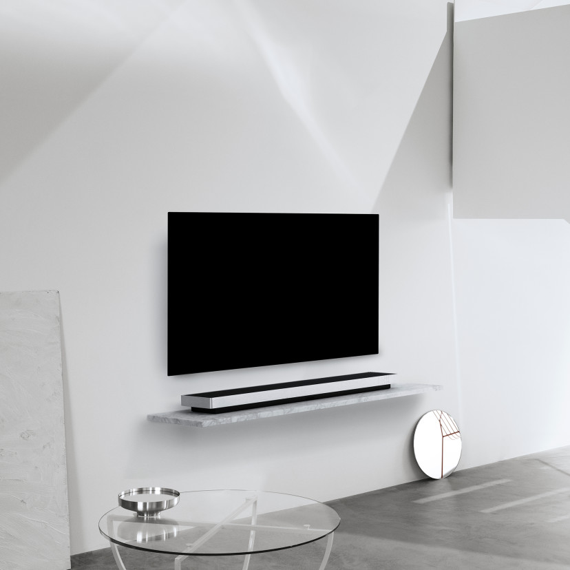 Soundbar on a surface and a TV mounted on the wall