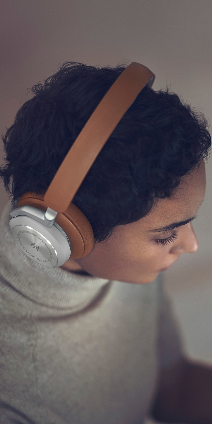 A woman wearing Beoplay HX Timber while working