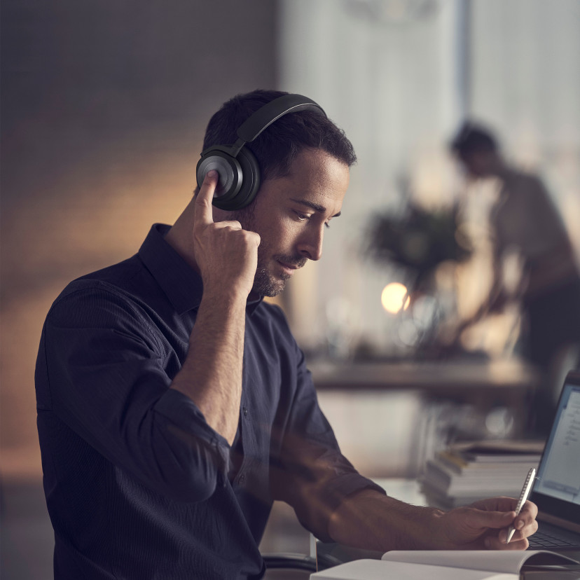 A man using Beoplay HX's touch interface to activate noise cancellation while working from home