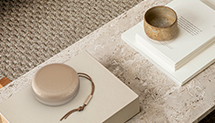 Beosound A1 bluetooth speaker in golden version on a marble table stacked on books