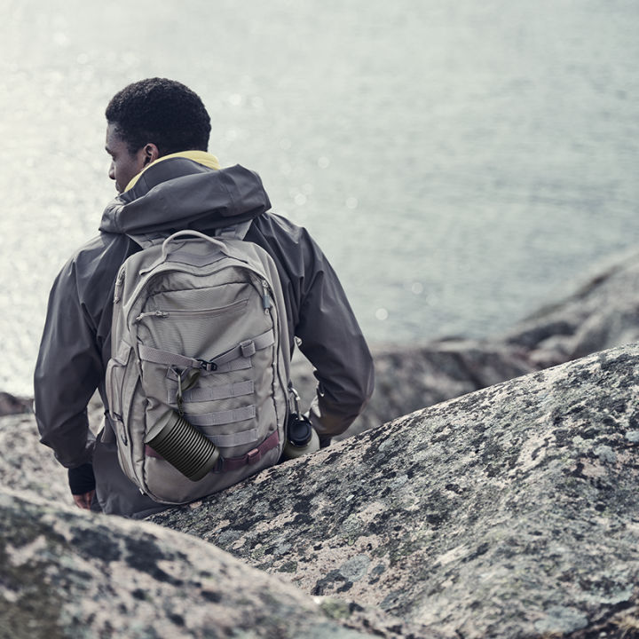 A person carrying Beosound Explore outdoor speaker while hiking