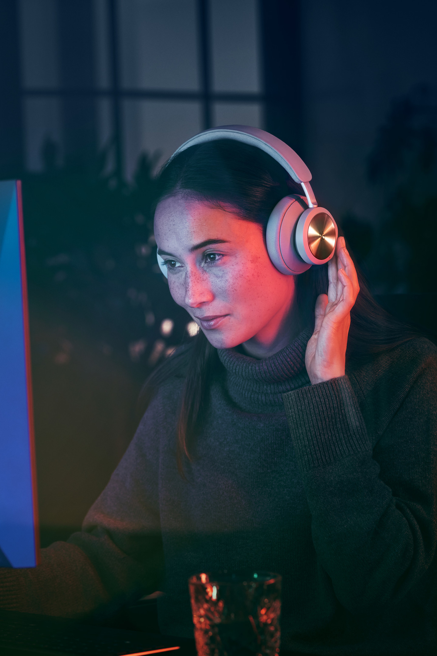 Woman gaming on her computer with Beoplay Portal on, while she uses the touch controls on the earcup
