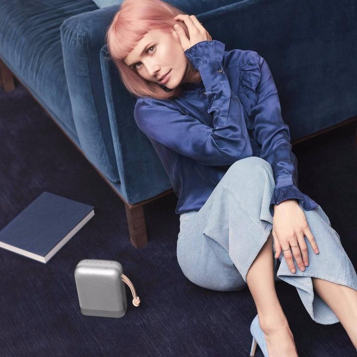 Kvinde i blåt, der sidder ved siden af sofa og Beoplay P6