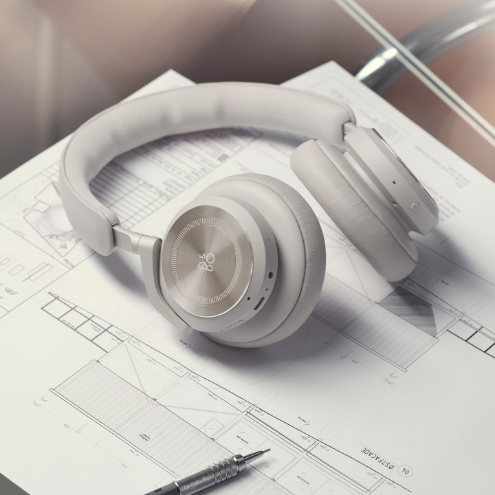 The headphones Beoplay HX laying on a desk with work documents