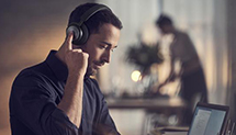 Man activating noise cancelling function on Beoplay HX headphones