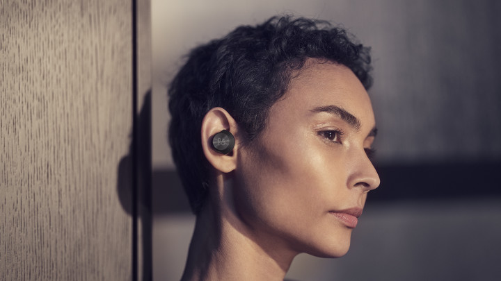 A woman wearing Beoplay EQ earphones.