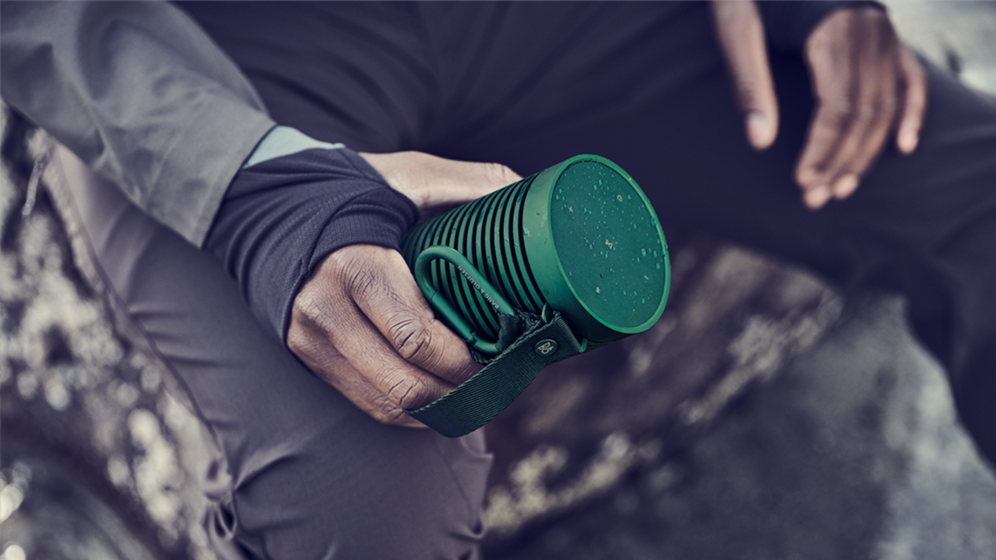 A man holds firmly Beosound Explore in green, before re-starting his hike